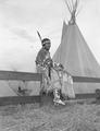 Young Native American woman sitting on fence rail