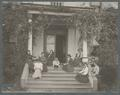 Women sitting on the front porch and steps of Alpha Hall