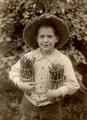 An unidentified child holding asparagus, circa 1940