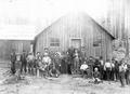 Loggers in front of logging camp building
