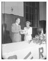 Irene Carl receives a radio gift from Ralph Floberg