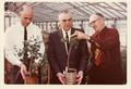 Roy Young with colleagues in greenhouse