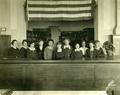 Library staff standing behind desk, 1921