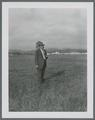 Harry Schoth standing on the original plot of alta tall fescue, 1950