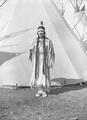 Young Native American woman standing next to tepee