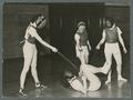 Three women pinning one to the ground in fencing class, 1938