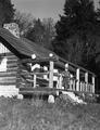 Peavy Cabin with George Peavy standing on step