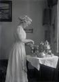 Rachel Morgan Gifford standing next to table with silver coffee service