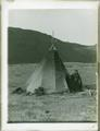 Woman standing next to tepee (along Columbia River?)