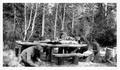 Four men building log table and benches