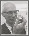M. Lowell Edwards holding an artificial heart valve, circa 1965