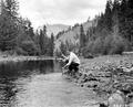 E. D. Cox fishing in the Umatilla River at Buck Creek Organization Camp, Umatilla National Forest