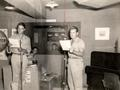 Broadcasting at an armed forces radio station, January 24, 1945. On the right is Captain Franklin K. Tourtellotte.