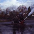 Four firemen using a water cannon